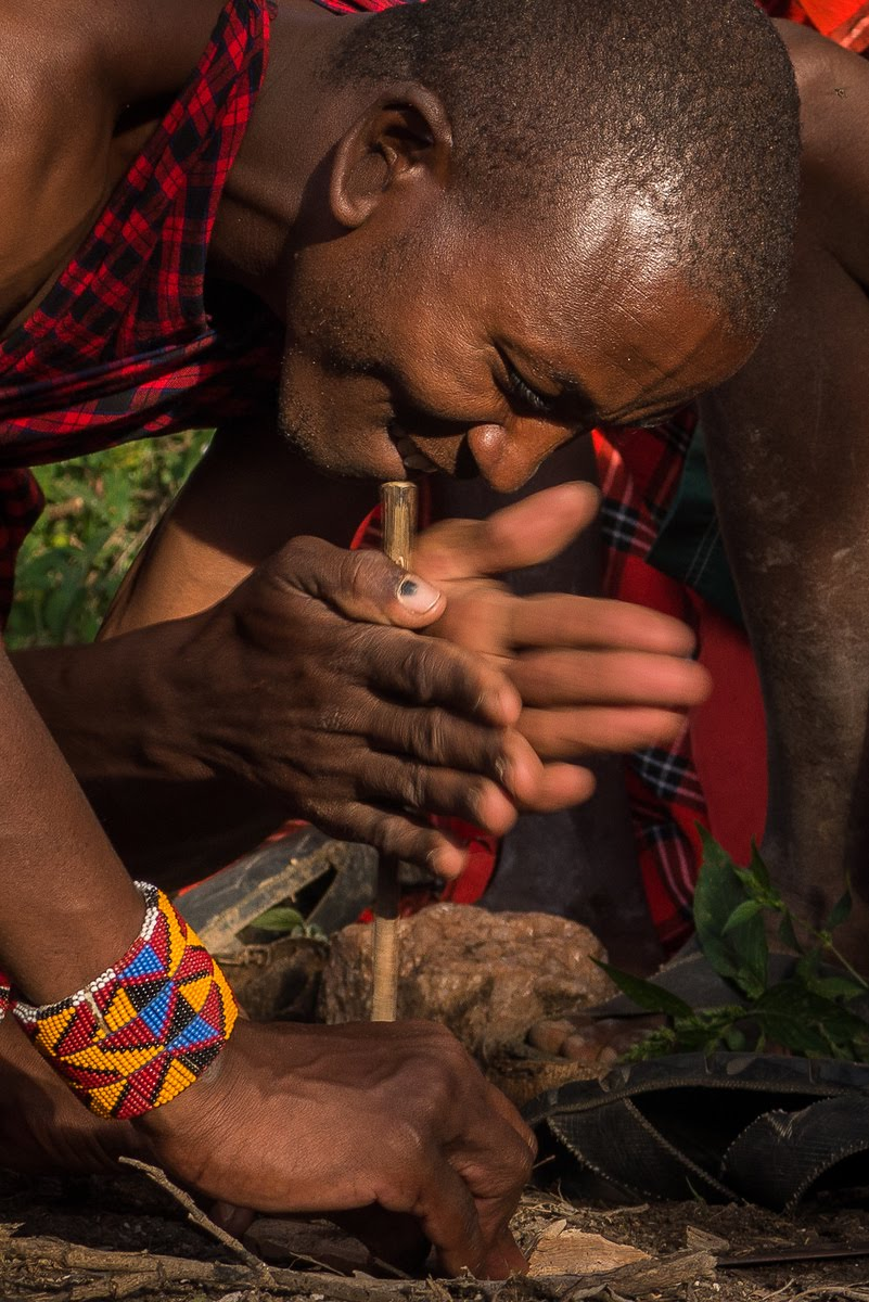One of the Maasai warriors spins the stick quickly to create friction!
